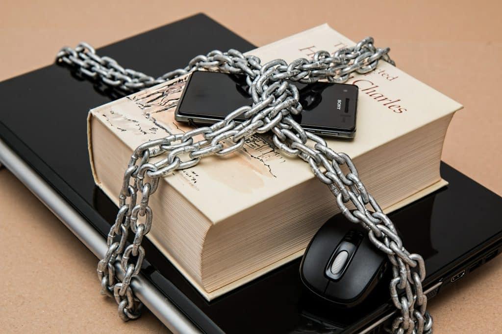 Laptop, książka i telefon spięte grubym łańcuchem symbolizując cenzurę